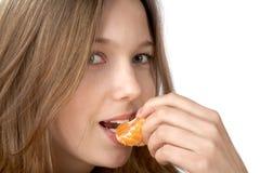 The girl  eat segment of  tangerine Royalty Free Stock Images