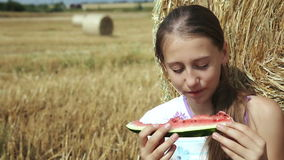 Girl eat watermelon near the haystack stock video footage