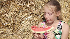Girl eat watermelon near the haystack stock footage