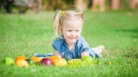 Girl eaten colorful fruits outside on green grass Stock Photography