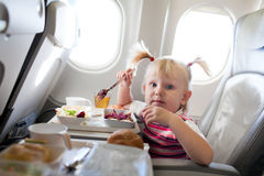 Girl eating in the airplane Stock Photo