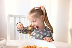 Girl eating with appetite. Tasty breakfast for children. stock photo
