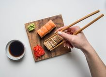 Girl eating an appetizing sushi set with ginger, soy sauce and wasabi on a white background royalty free stock photos