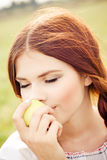 Girl eating an apple. Young pretty girl eating an apple Royalty Free Stock Images