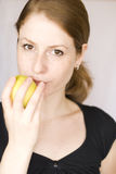 Girl eating an apple. Young girl living healthy, eating an apple Royalty Free Stock Images