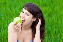 Girl eating an apple. Girl eating a green apple on a grass Royalty Free Stock Images