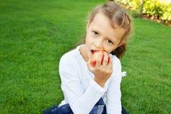 Girl eating an apple Stock Image