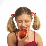 Girl eating an apple. Blond girl eating an apple Royalty Free Stock Image