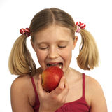 Girl eating an apple. Blond girl eating an apple Royalty Free Stock Photos