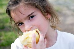 Girl Eating an Apple. A young girl having a snack stock photography