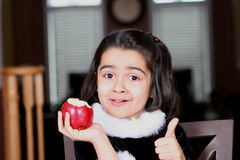 Girl eating apple and enjoying. Sweet and cute girl eating apple Stock Images