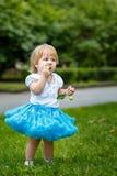 Girl eating an apple. Little blond girl in a blue skirt eating an apple Stock Image