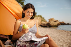 Girl eating apple and reading book at the beach camping Royalty Free Stock Photo
