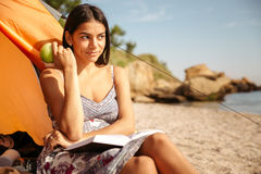 Girl eating apple and reading book at the beach camping Royalty Free Stock Photos