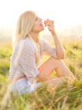 Girl is eating apple sitting on green field Stock Photos