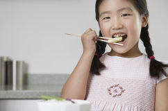 Girl Eating Baby Corn With Chopsticks Stock Images