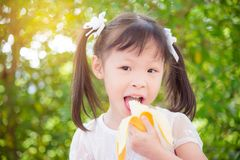 Girl eating banana and smiles between picnic in park. Little asian girl eating banana and smiles between picnic in park stock image
