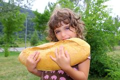 Girl eating big bread humor size hungry child. Funny gesture royalty free stock photo