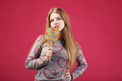 Girl eating big striped lollipop Stock Photography