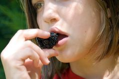 Girl Eating a Blackberry stock photo