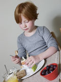 Girl Eating Boiled Egg At Dining Table Stock Images