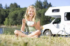 Girl (9-11) eating from bowl on grass with legs crossed, motor home in background, smiling, portrait Royalty Free Stock Photo