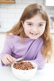 Girl Eating Bowl Of Sugary Breakfast Cereal In Kitchen. Girl Eats Bowl Of Sugary Breakfast Cereal In Kitchen Royalty Free Stock Image