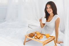 Girl eating breakfast in bed Stock Photos