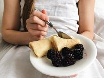 Girl eating breakfast in bed Stock Photography