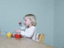 Girl Eating Breakfast At Dining Table Stock Photos