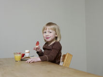 Girl Eating Breakfast At Dining Table Stock Images
