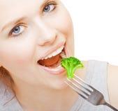 Girl eating broccoli Stock Photos