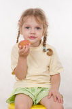 Girl eating a bun sitting on chair Royalty Free Stock Photos