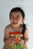 Girl eating burger. Little chinese girl laughing and eating a hamburger Stock Image