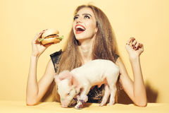 Girl eating burger with pig Royalty Free Stock Images
