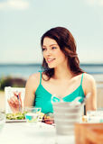 Girl eating in cafe on the beach Royalty Free Stock Photo