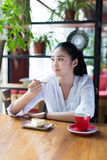 Girl eating a cake in cafe Royalty Free Stock Photography
