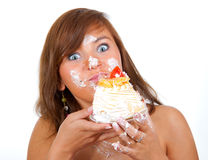 Girl eating cake with his hands royalty free stock photos