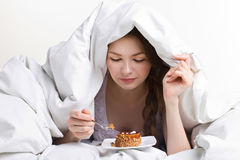 Girl eating cake under cover Stock Photos
