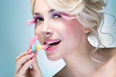 Girl eating candy. Girl with bright makeup eating candy Royalty Free Stock Photos