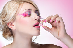 Girl eating candy. Girl with bright makeup eating candy Stock Photos