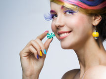 Girl eating candy. Girl with bright makeup eating candy Royalty Free Stock Image