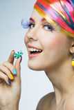 Girl eating candy. Girl with bright makeup eating candy Stock Images