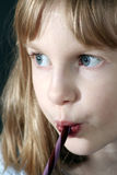 Girl eating Candy Cane royalty free stock image
