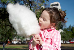 Girl eating candy-floss Stock Photos