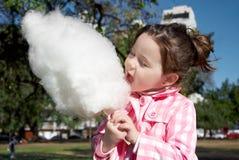 Girl eating candy-floss Stock Photos