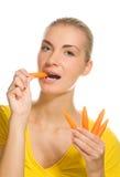Girl eating carrot Stock Images