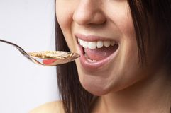 Girl eating cereal. Close up of young girl eating a spoonful of bran flakes cereal. See all my food & drink images here stock photo