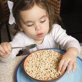 Girl eating cereal. Royalty Free Stock Images