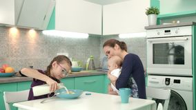 Girl eating cereal breakfast with mother and baby boy. Family breakfast time stock video